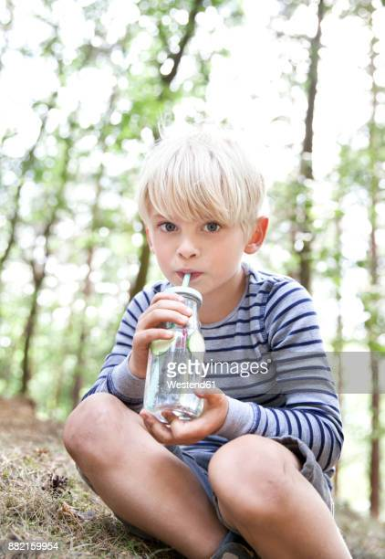 Boy drinking from glass of infused water in forest