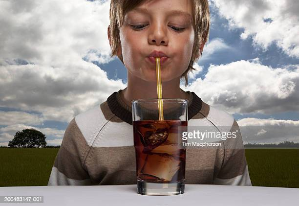 Boy (8-10) drinking glass of cola in countryside, close-up (Digital Composite)