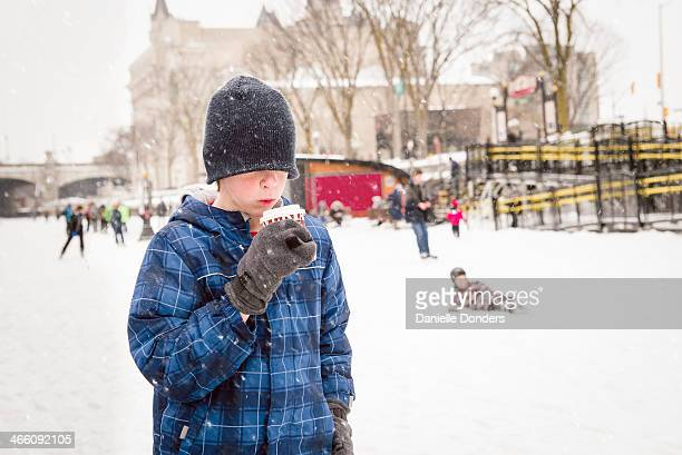 """boy drinking hot chocolate on the rideau canal - """"danielle donders"""" stock pictures, royalty-free photos & images"""