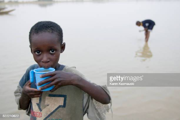 Boy Drinking Lakewater From Cup