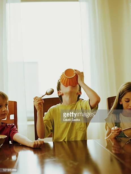 Boy (6-8) drinking milk from bowl, siblings (4-9) sitting beside him