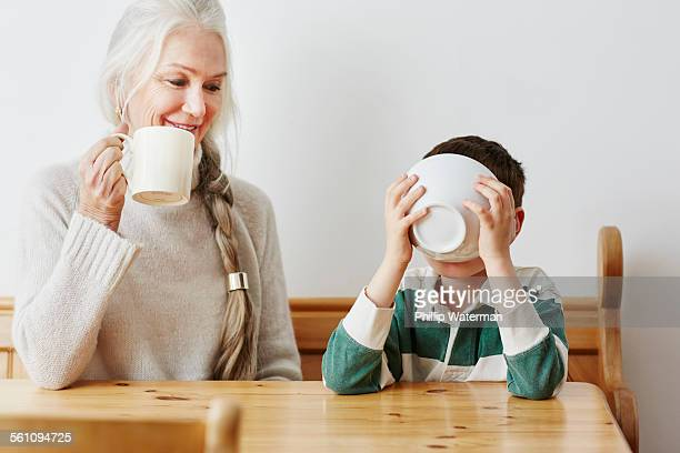 Boy drinking milk from bowl with grandmother