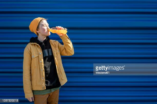 boy drinking orange juice while standing against blue shutter during sunny day - juice drink stock pictures, royalty-free photos & images