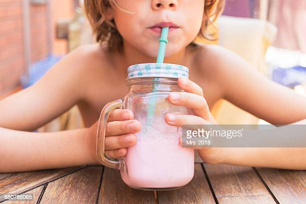 Boy drinking strawberry milkshake from a mason jar