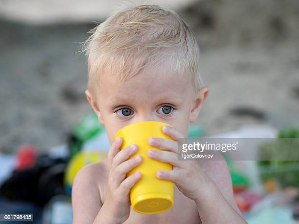 Boy drinking water from plastic cup on beach