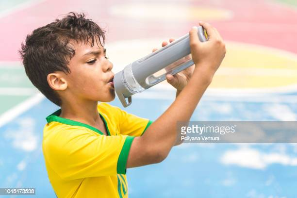 boy drinking water on court - thirsty stock pictures, royalty-free photos & images