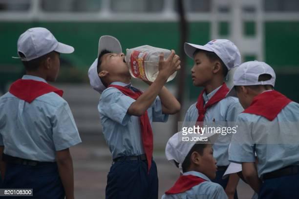 A boy drinks from a bottle on a street in Pyongyang on July 21 2017 / AFP PHOTO / Ed JONES