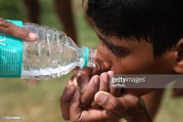 Boy drinks water from a bottle on a hot summer day in New Delhi, India on 15, June 2019