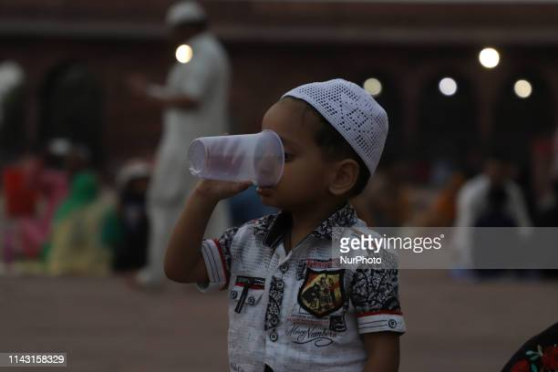 A boy drinks water from a disposable glass as Muslims break their daylong fast in New Delhi India Saturday May 12 2019 Muslims across the world are...