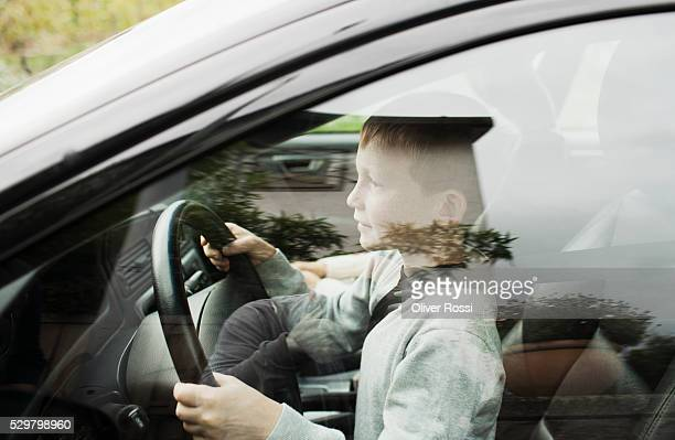 Boy (10-12) driving car