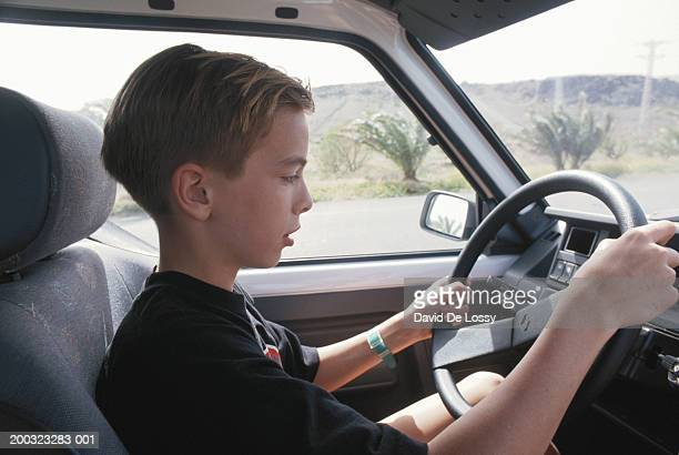 Boy (12-13) driving car, side view, close-up