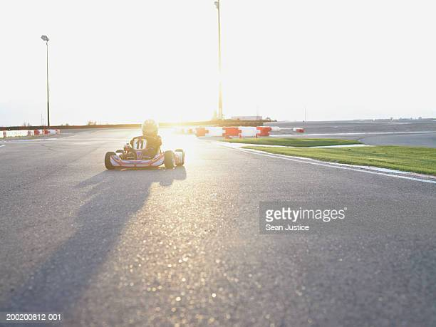 Boy (6-8) driving go-cart on track