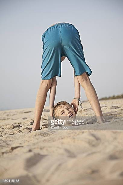 Boy drops his head on the beach in Dubai