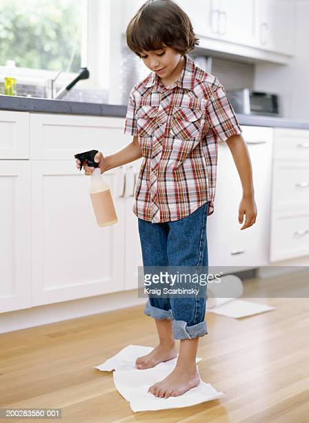 Boy (5-7) drying kitchen floor with paper towel under feet, smiling