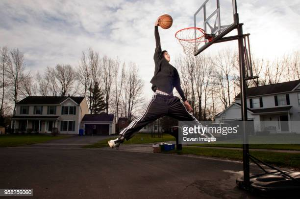 boy dunking ball in hoop on road - shooting baskets stock pictures, royalty-free photos & images