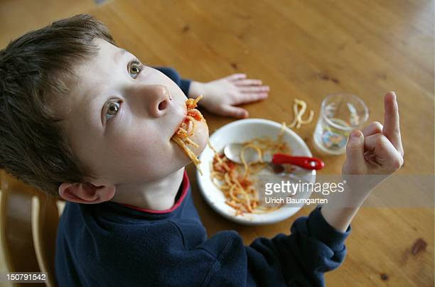 Boy eat spaghetti with gesture fuck you Symbol picture about bad behave bad table manners of children