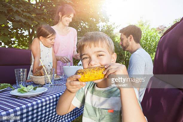 Boy eating a corn cob on a family barbecue in garden