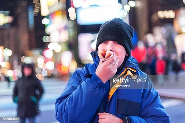 ragazzo mangia un hot-dog a new york city - abbuffata foto e immagini stock