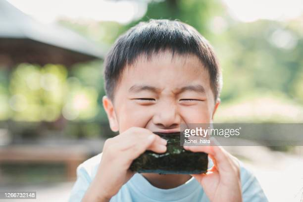 boy eating a rice ball outdoors - rice ball stock pictures, royalty-free photos & images