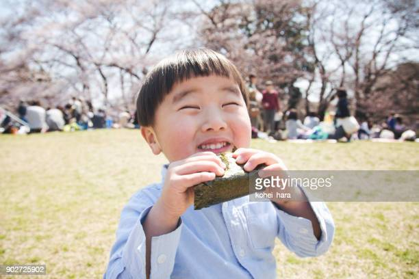 boy eating a rice bowl in the park - childhood stock pictures, royalty-free photos & images