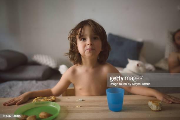 boy eating and watching tv - bebe desnudo fotografías e imágenes de stock
