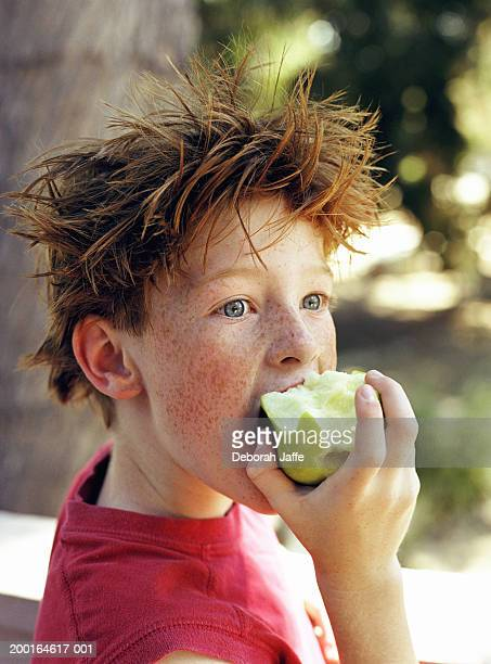 Boy (8-10) eating apple, close-up