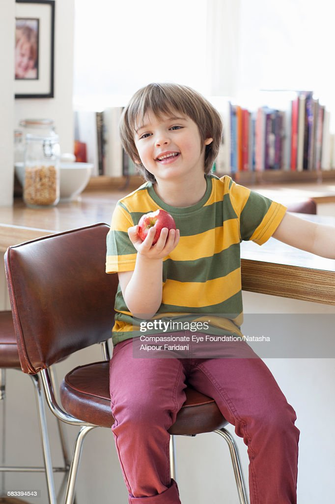 Boy eating apple in kitchen : Stock Photo