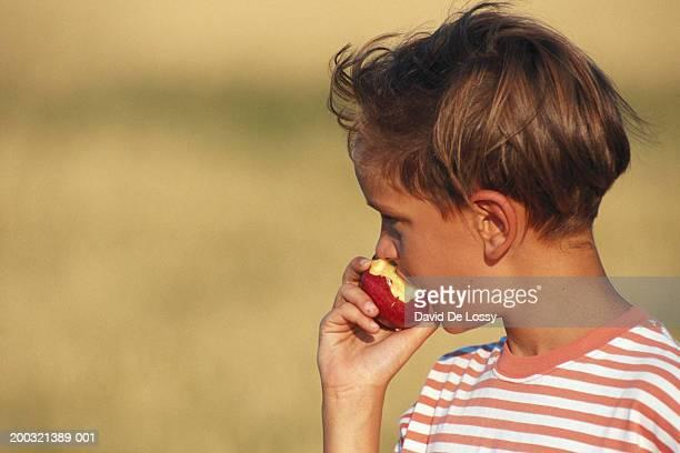 Boy (8-9) eating apple, looking away