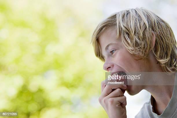 Boy (10-12) eating apple profile
