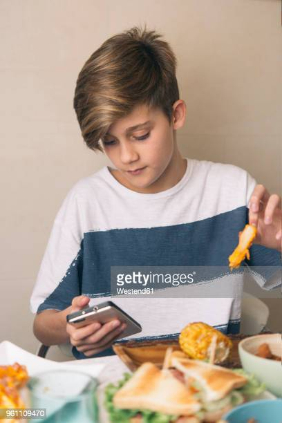 Boy eating at dining table and looking at the phone at the same time