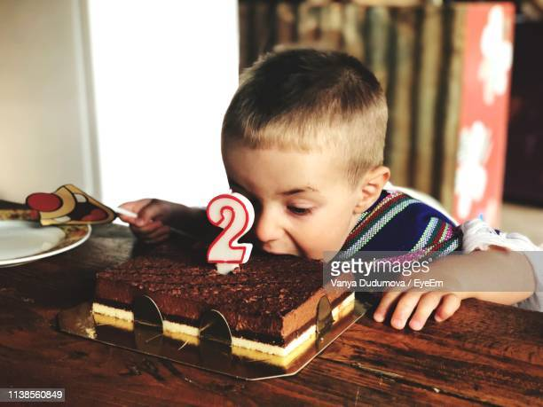 boy eating birthday cake at table - number 2 stock pictures, royalty-free photos & images