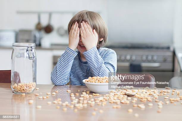 Boy eating bowl of cereal in kitchen