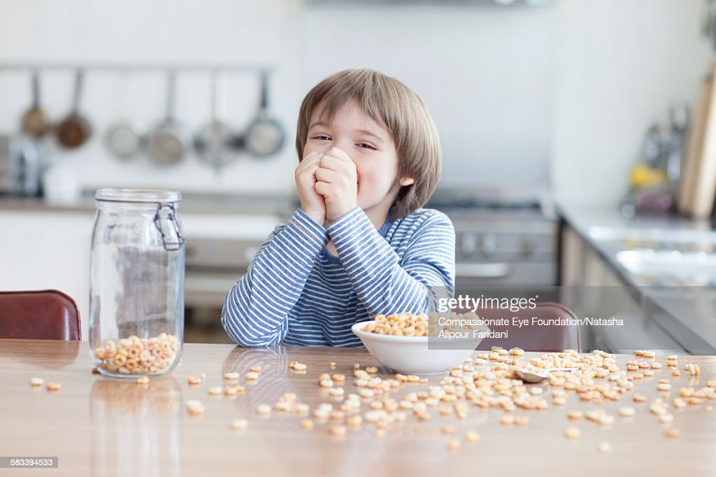 Boy eating bowl of cereal in kitchen : Stock Photo