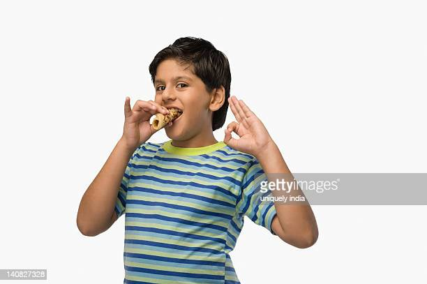 Boy eating bread and showing ok sign