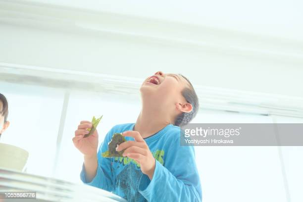boy eating breakfast at home - nori stock pictures, royalty-free photos & images