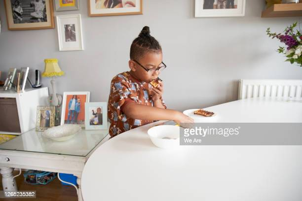 boy eating breakfast at home - routine stock pictures, royalty-free photos & images