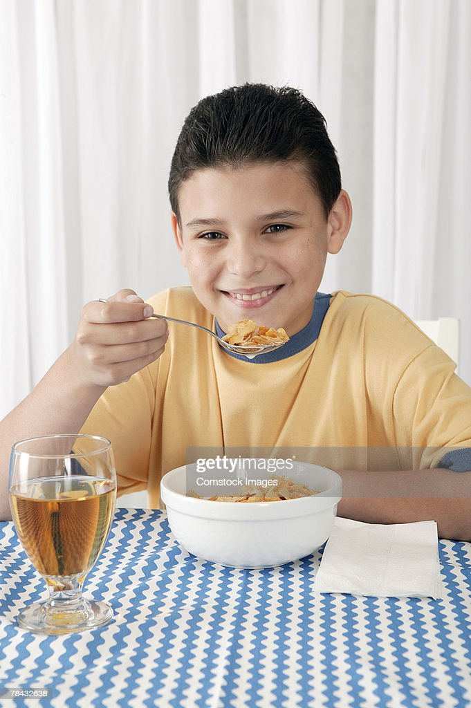 Boy eating breakfast cereal at table : Stockfoto