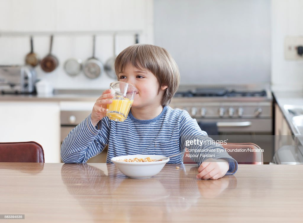 Boy eating breakfast in kitchen : Stock Photo