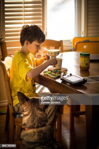 Boy eating breakfast in the sun while a dog watches