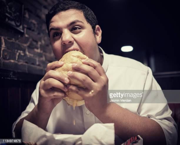 boy eating burger at restaurant - jordanian workforce stock pictures, royalty-free photos & images