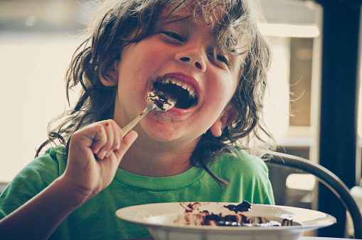 Boy eating cake at a cafe. - gettyimageskorea