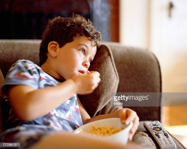 Boy eating Cereal on Couch