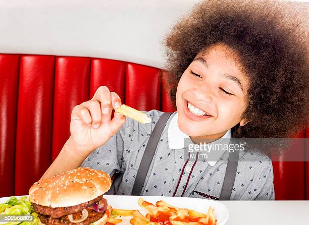 boy (10-11 years) eating chips in diner - 10 11 years stock pictures, royalty-free photos & images