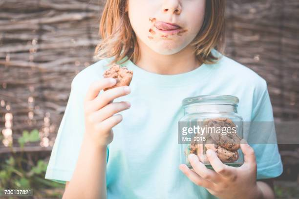 Boy eating chocolate cookie while holding a jar of cookies