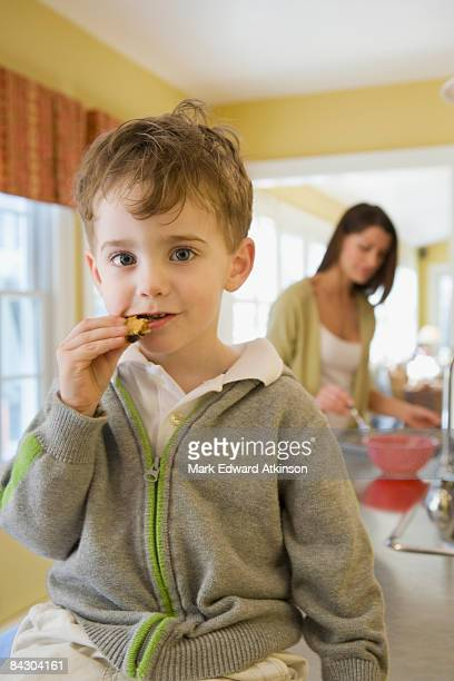 Boy eating cookie on kitchen counter