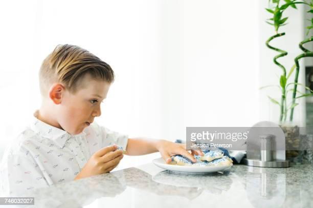 Boy (8-9) eating cookies