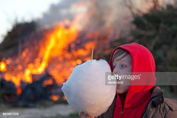 boy eating cotton candy in front of Easter eve bonfire Neetze Lower Saxony Germany