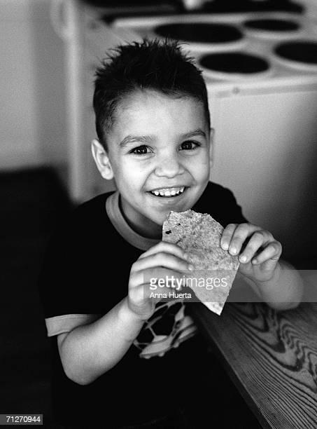 Boy eating crispbread in the kitchen.