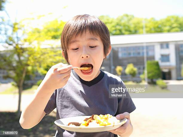Boy (6-7) eating curry in school playground