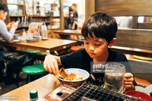 Boy eating food at Japanese restaurant in Tokyo